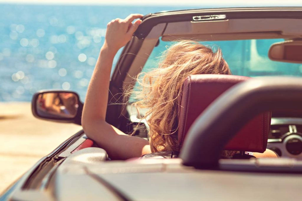 woman in car with top down convertible driving to the beach