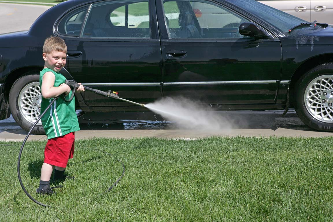 young boy power washing a black car in his driveway instead of going to a local car wash