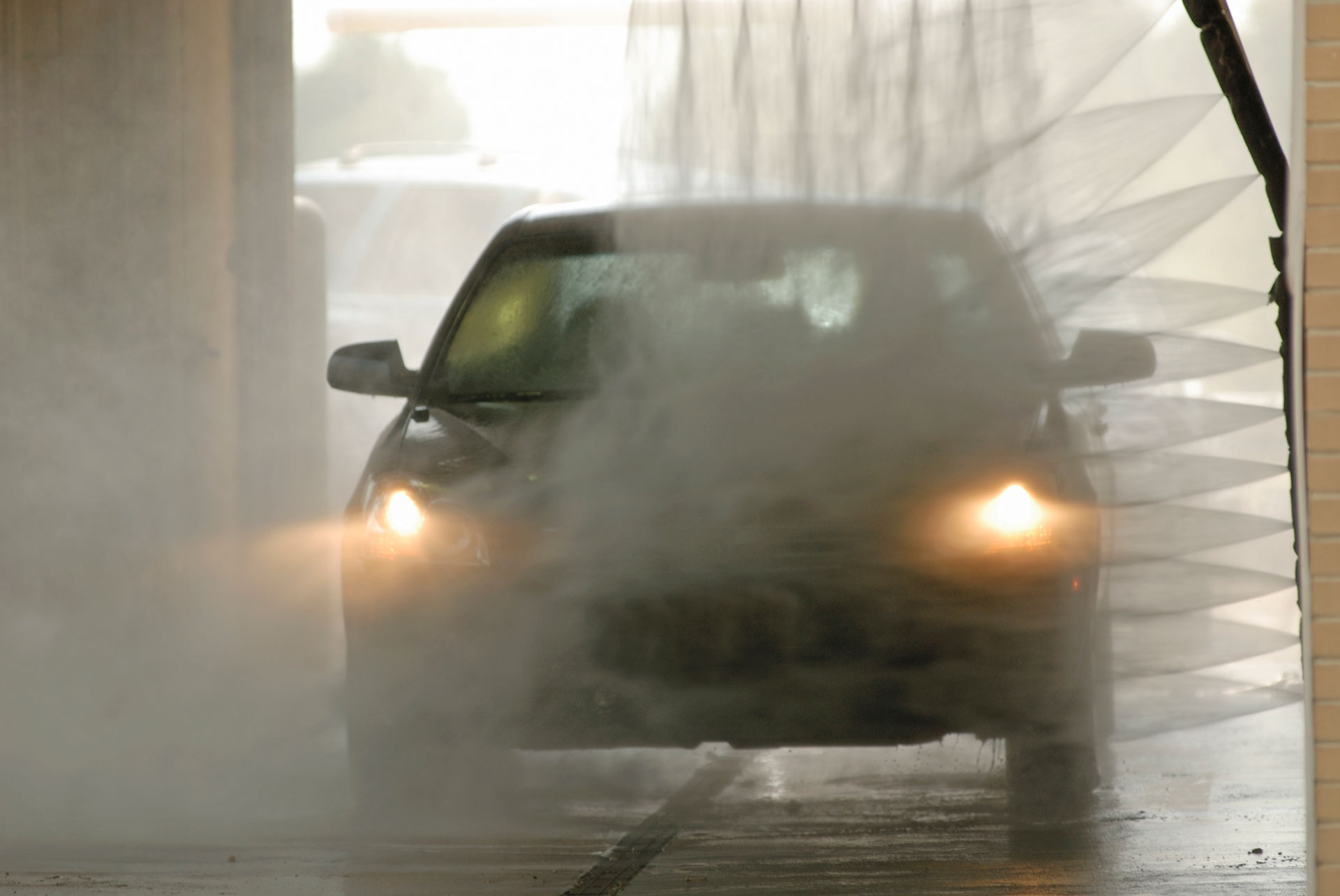 High pressure water jets clean a car in an automatic touchless car wash